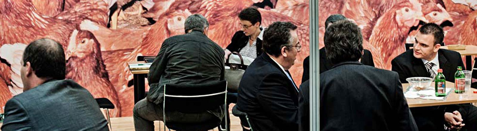 Vor einer Wand, auf der Hühner abgebildet sind, sitzen Männer und eine Frau in dunkler Business-Kleidung. Sie sitzen an Tischen und reden miteinander.
