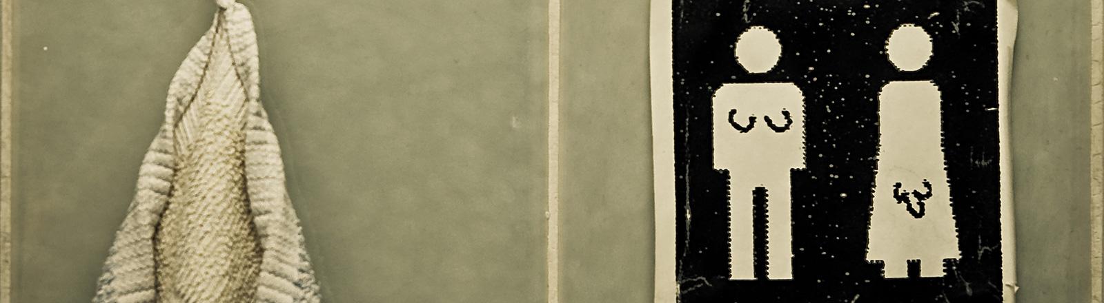 Auf Fliesen in einem Badezimmer hängt ein Schild, das Piktogramme einer Frau und eines Mannes zeigt. Der Frau wurde ein Penis gezeichnet und dem Mann ein Busen.