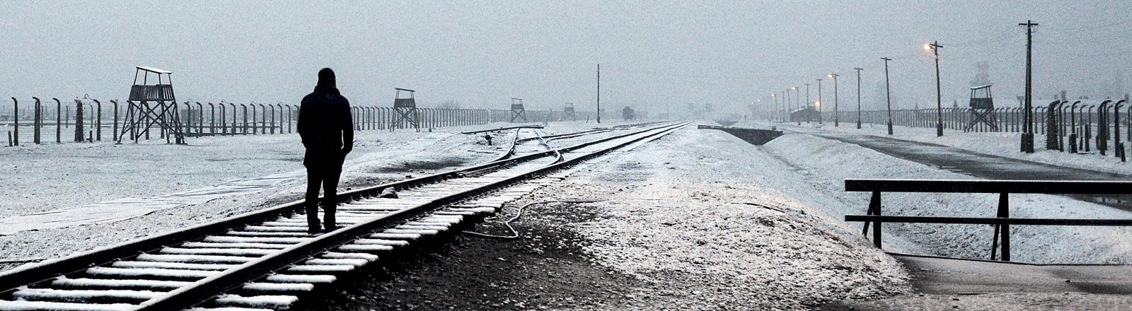 Ein Besucher steht an den Gleisen im Konzentrationslager Auschwitz-Birkenau. Der Himmel ist grau, es liegt etwas Schnee. Links und rechts von den Gleisen sind Zäune und Überwachungstürme; Bild: dpa