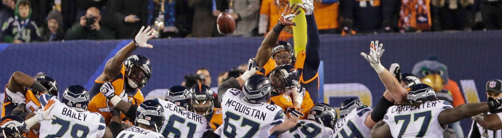 Szene des Super Bowls 2014. Ein Haufen American Football-Spieler kämpfen um den ellipsenförmigen Ball; Bild: dpa