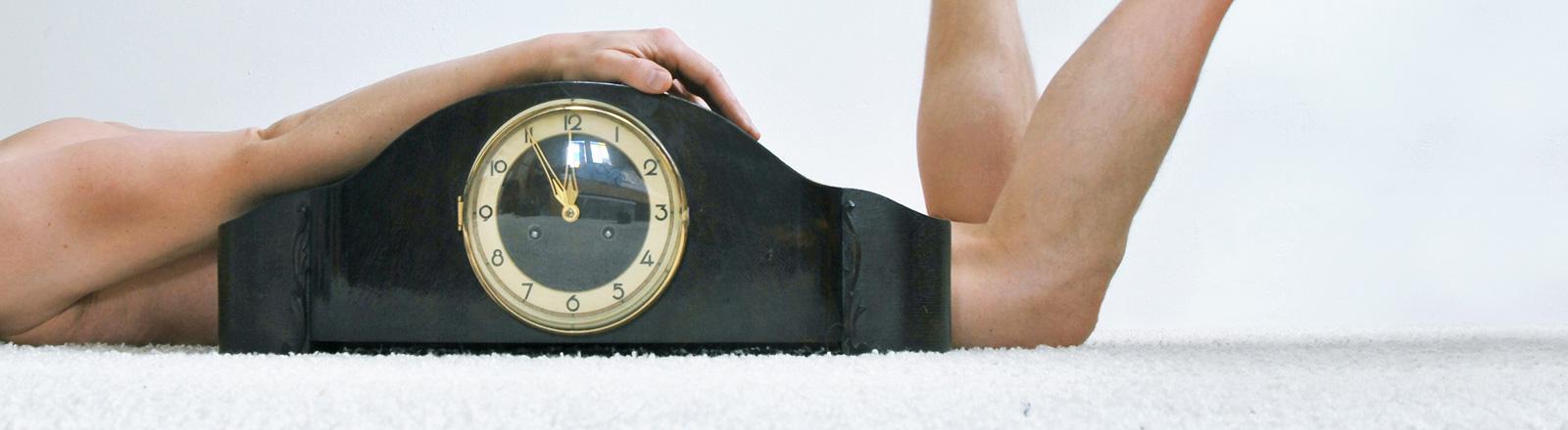 Auf einem weißen Fußboden liegt ein nackter Mann auf dem Bauch. Direkt neben ihm steht eine große Holzuhr, die seinen Körper verdeckt.