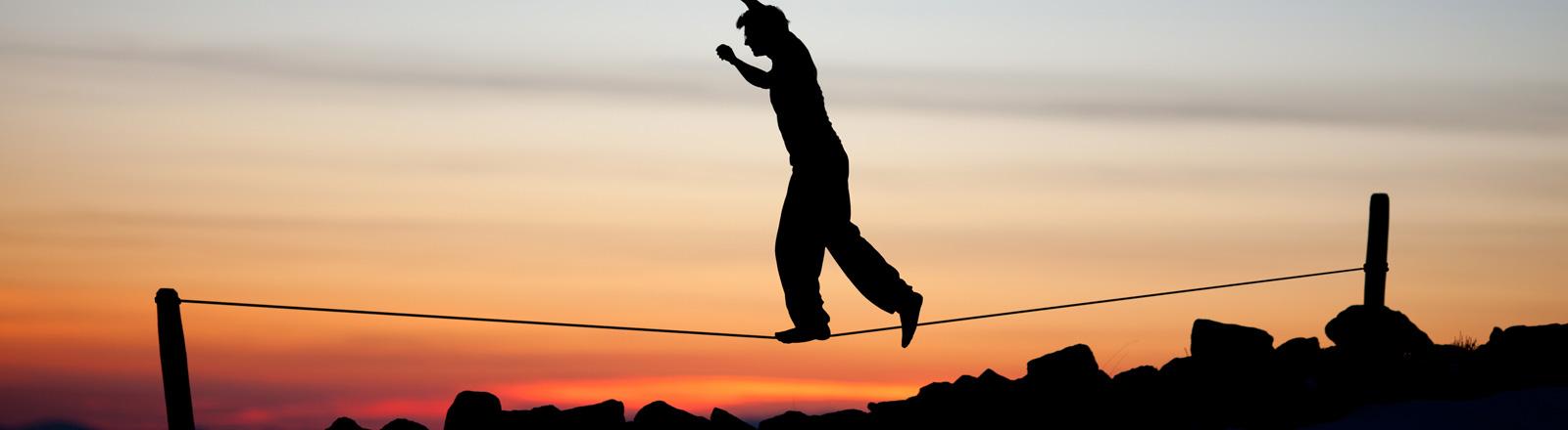 Die schwarze Silhouette eines Mannes zeichnet sich vor der Abendsonne ab. Er balanciert auf einer Slackline, einem gespannten Band.
