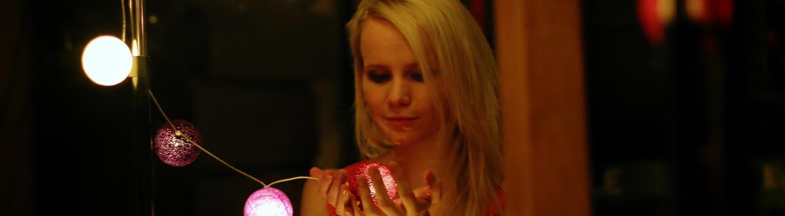 Eine Frau hält einen leuchtenden Lampion in der Hand.