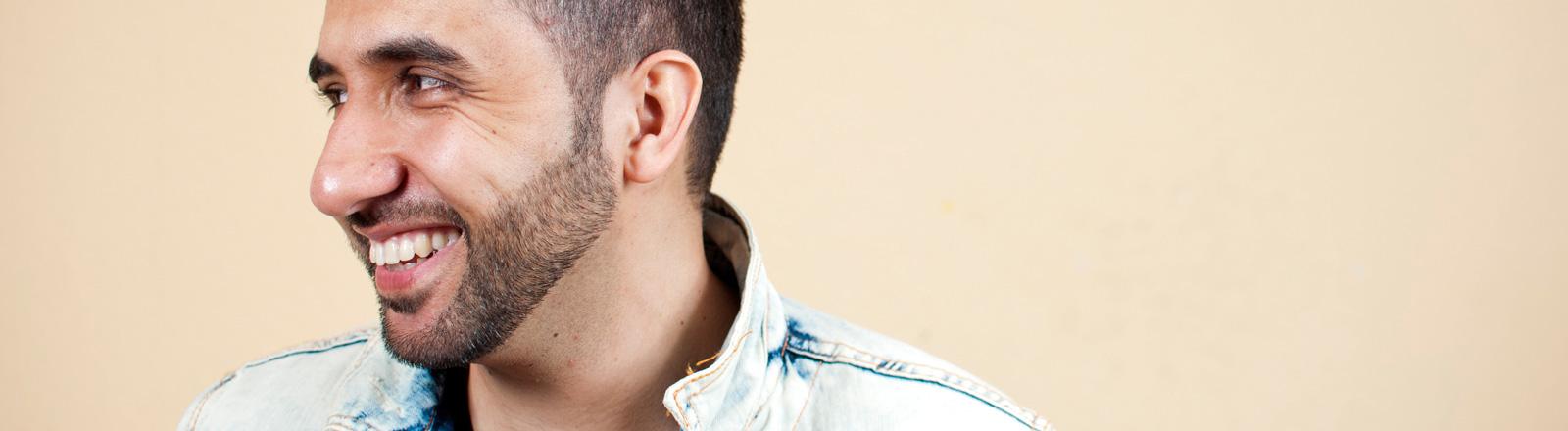 Ein junger Mann mit Bart und kurzen schwarzen Haaren ist im Profil zu sehen. Er grinst.