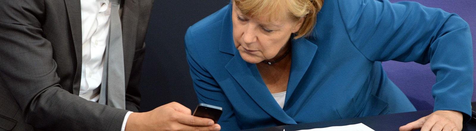 Der ehemalige Bundeswirtschaftsminister Philipp Rösler (FDP) zeigt Bundeskanzlerin Angela Merkel etwas auf seinem Smartphone.