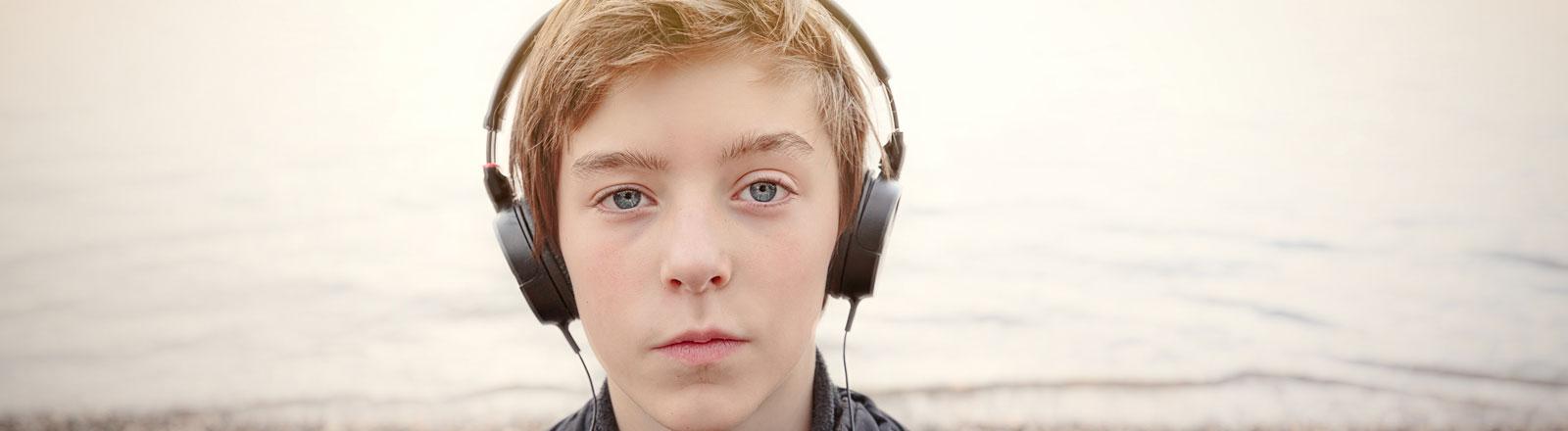 Ein Junge steht mit Kopfhörern am Rhein.