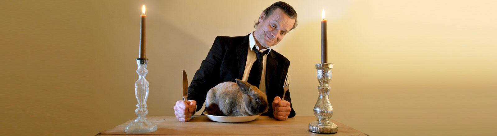 Ein Mann hat ein lebendiges Kaninchen auf seinem Teller sitzen.