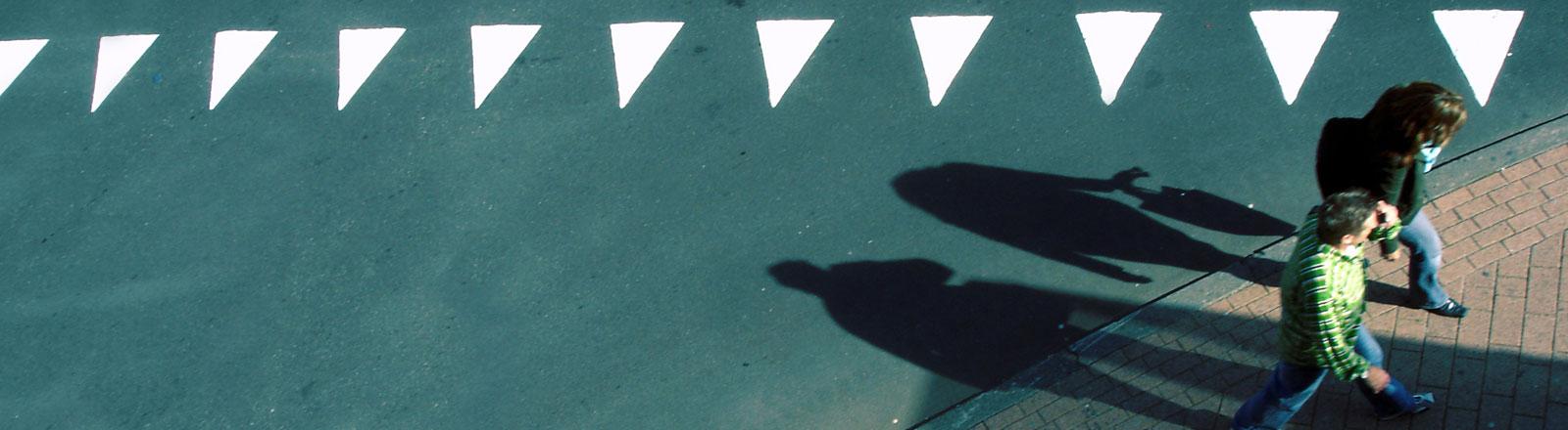 Ein Paar geht an einer Markierung aus Dreiecken vorbei.