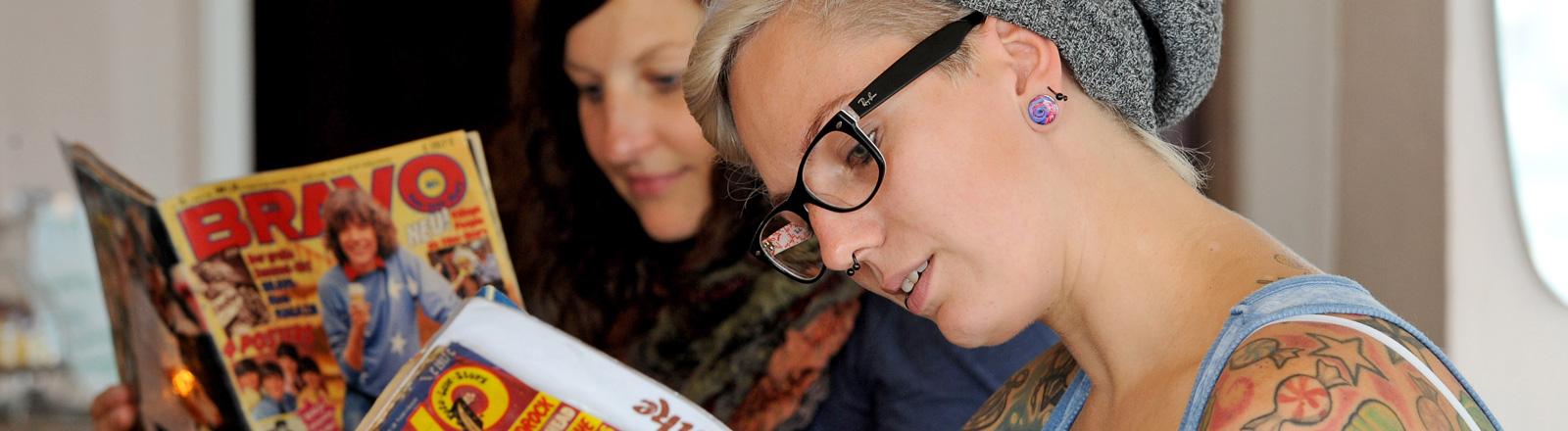 """Zwei junge Frauen lesen alte Ausgaben der Bravo in der Bremer Nostalgie-Kneipe """"Wohnzimmer"""", darin eingebunden ist die Getränkekarte. Die eine Frau hat viele Tattoos; Bild: dpa"""