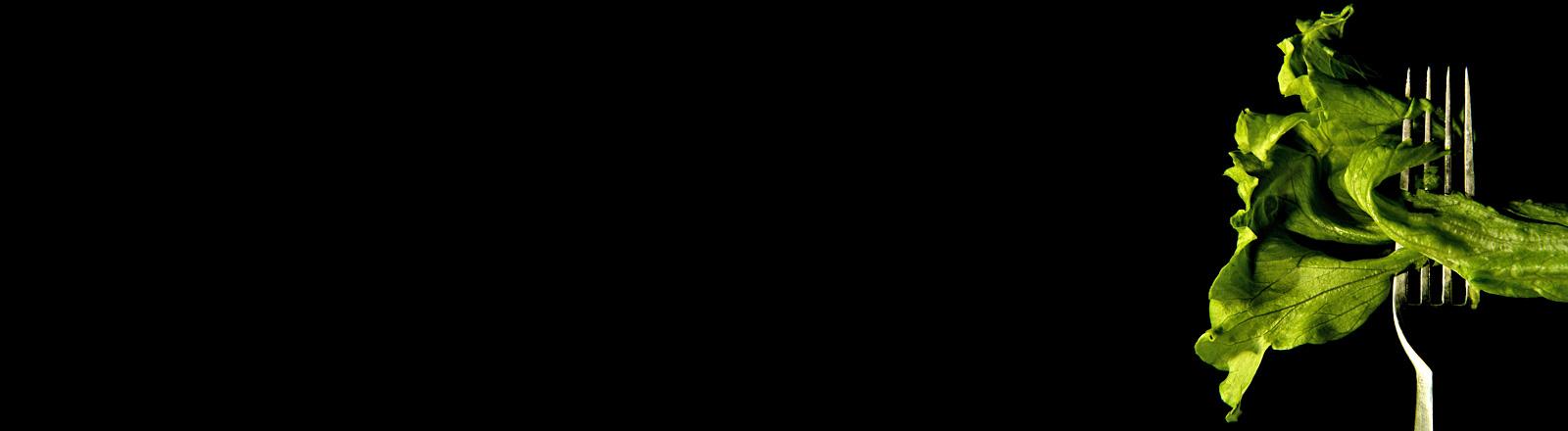 Auf schwarzem Hintergrund ist eine Gabel zu sehen, auf der ein Salatblatt aufgespießt ist.
