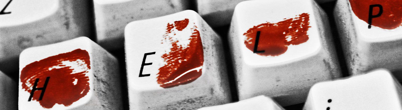 Eine Tastatur. Auf den Tasten für die Buchstaben H, E, L und P sind Blutflecken.