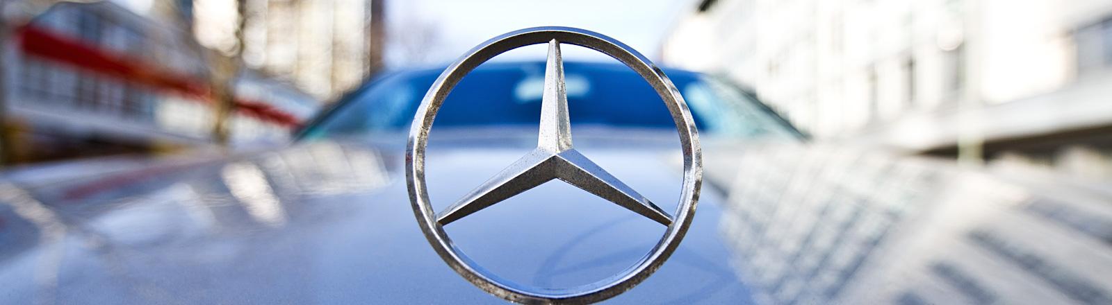 Blick auf einen Mercedes-Benz-Stern als Kühlerfigur, das Auto fährt durch eine Straße; Bild: dpa