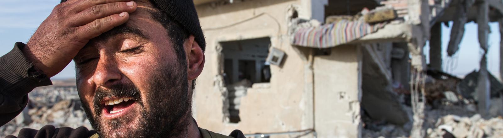 Ein Kämpfer der kurdischen YPG steht am 06.02.2015 in Kobane, Syrien, vor einem zerstörten Haus. Die schweren Kämpfe zwischen Kurden und Kämpfern des Islamischen Staates (IS) haben die Stadt in weiten Teilen in ein Trümmerfeld verwandelt.