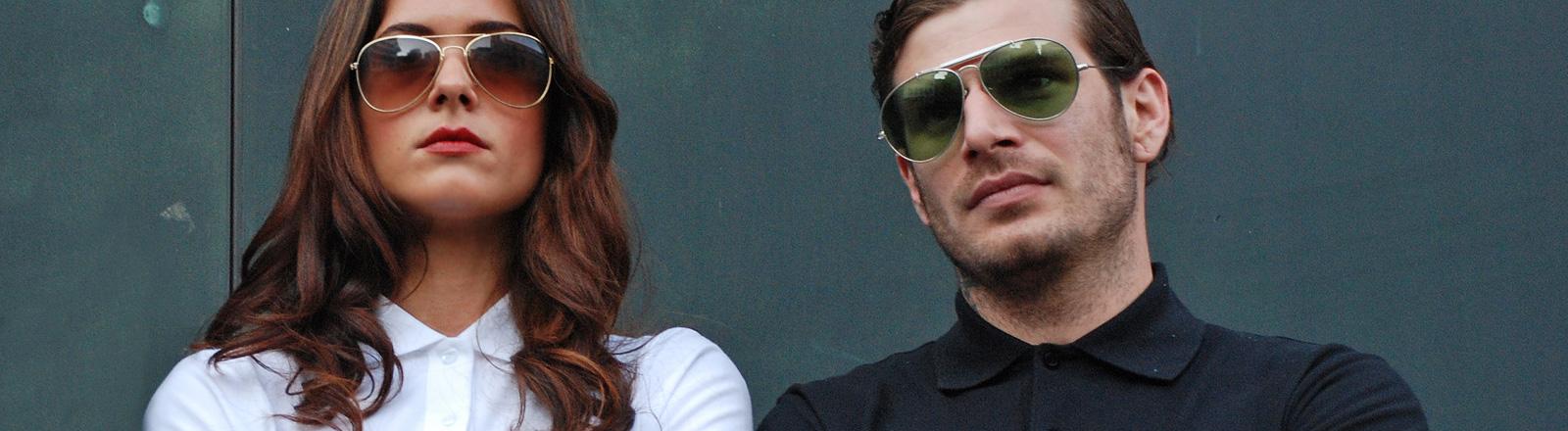 Eine Frau und ein Mann stehen nebeneinander. Sie haben nackte Unterarme mit Tattoos und tragen beide Polo-Shirt und Sonnenbrille. Die Arme halten sie verschränkt vor der Brust.