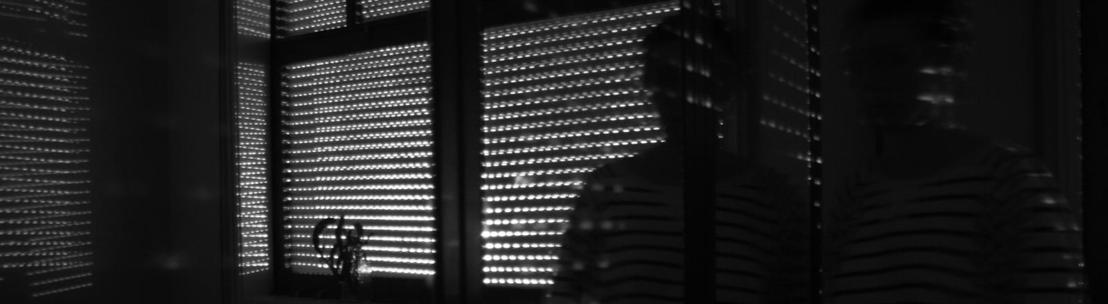 Eine Person setht in einem verdunkelten Raum.