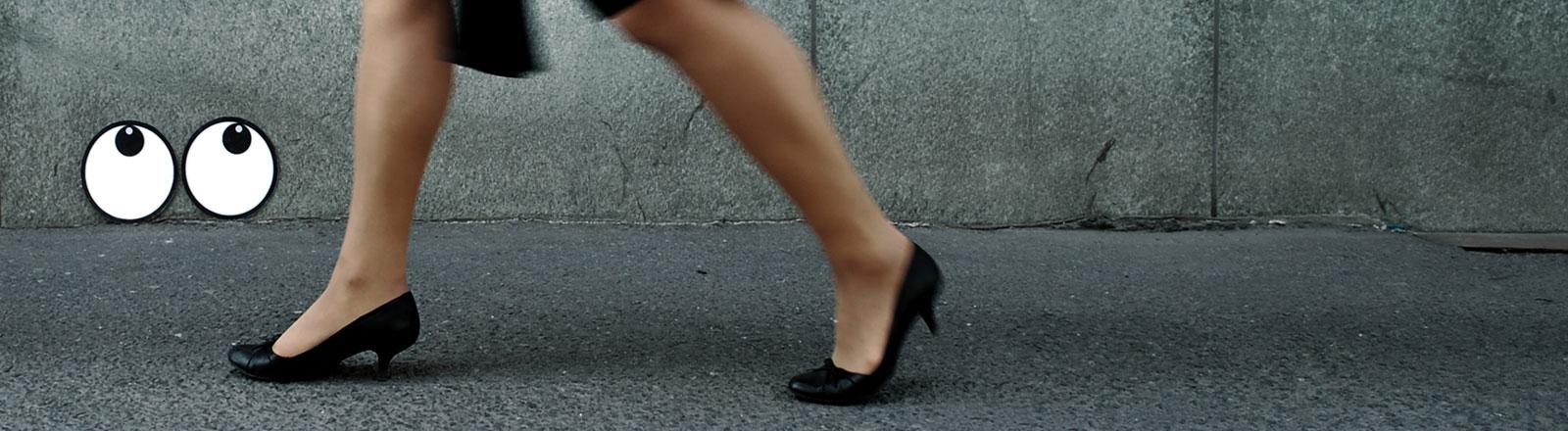 Eine Frau geht eine Straße entlang, zwei Graffiti-Augen beobachten sie dabei.
