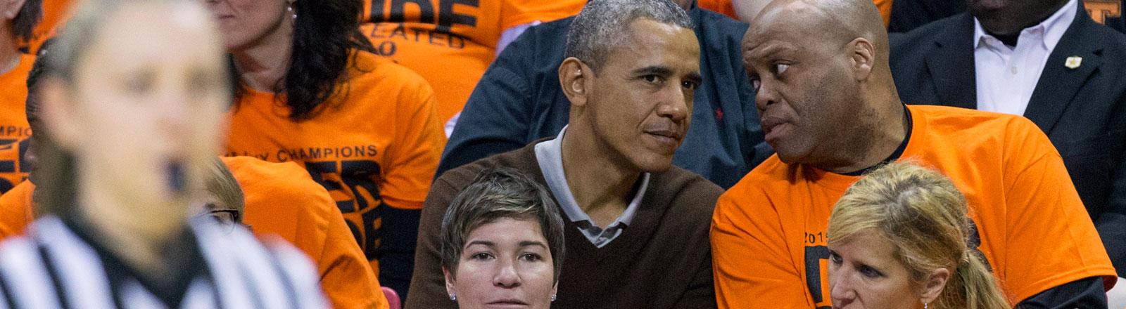 Barack Obama verfolgt mit seinem Schwager ein Spiel der NCAA.