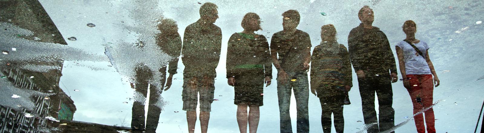 Ein Team aus Männern und Frauen spiegelt sich in einer Straßenpfütze.