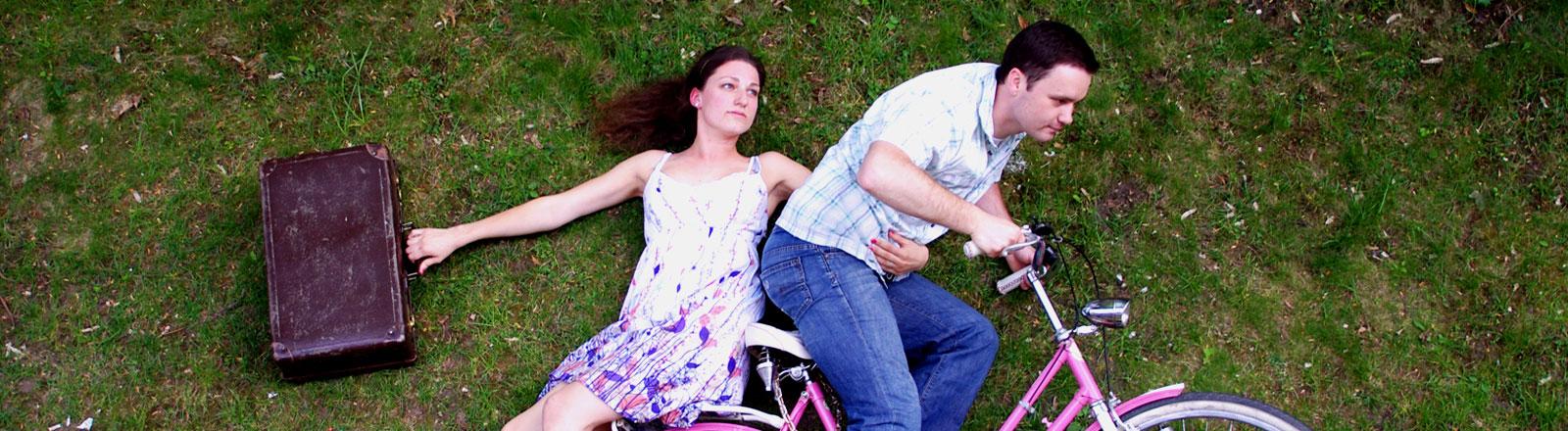 Junge Frau mit Koffer und junger Mann auf einem Fahrrad