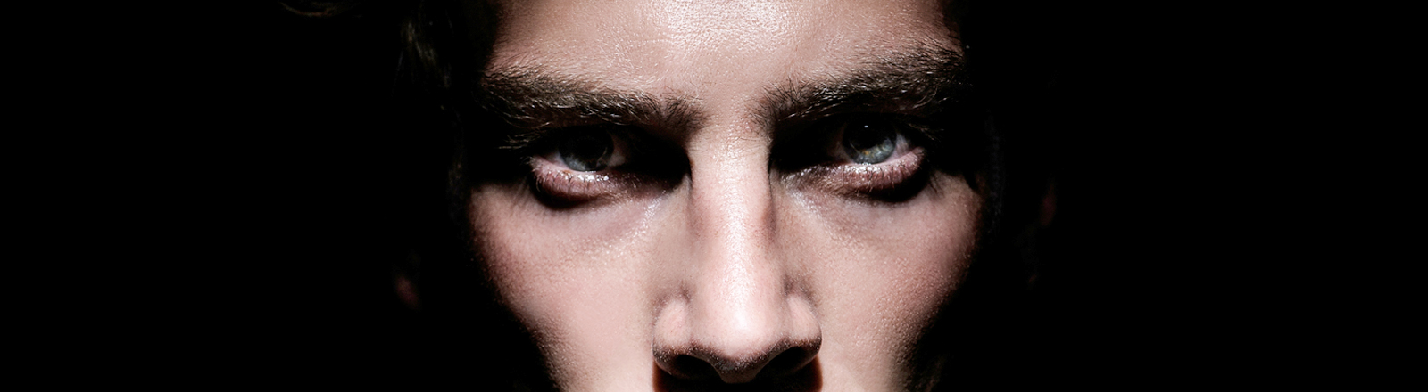 Ein Mann im Schatten schaut grimmig