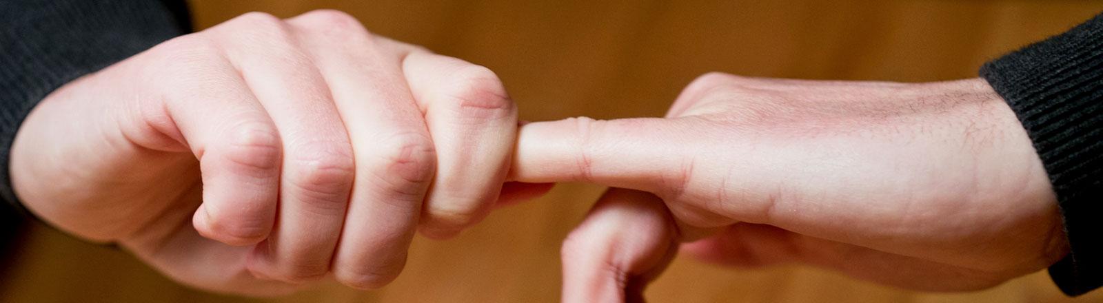 Zwei Hände: die eine zieht am Finger der anderen Hand