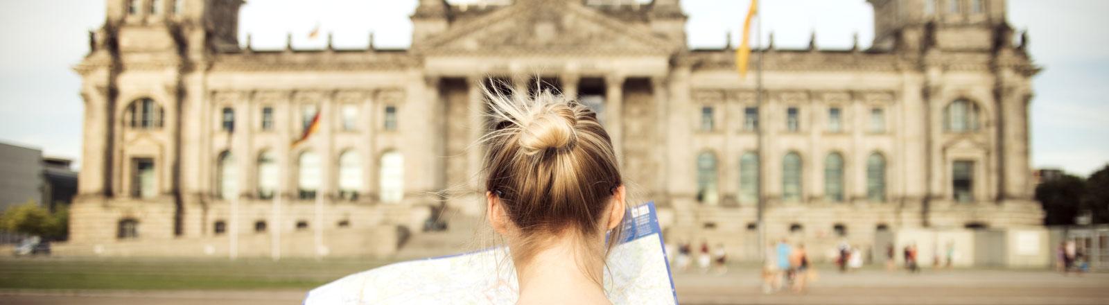 Junge Frau mit Stadtplan vor der Berliner Reichstag