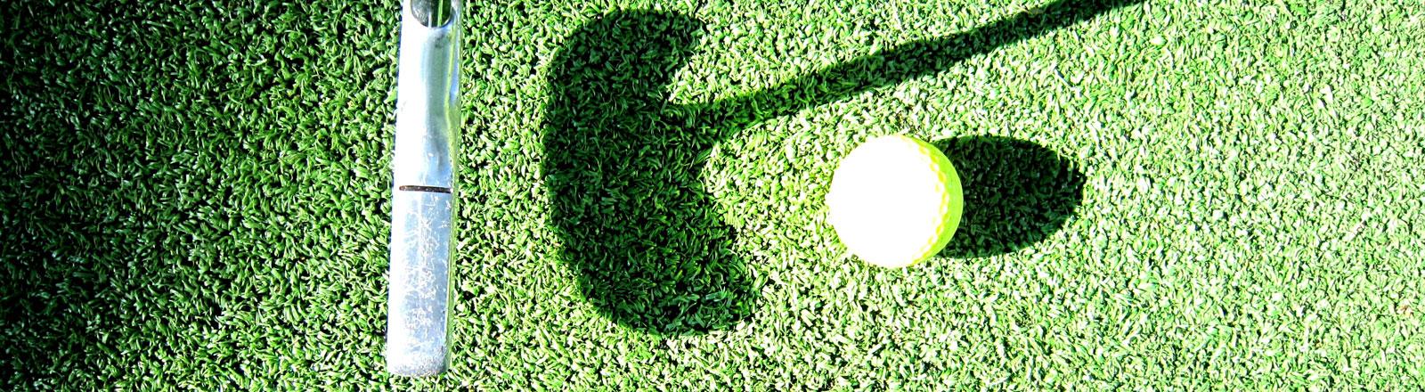 Ein Minigolfschläger mit einem Ball auf einem grünen Kunstrasen