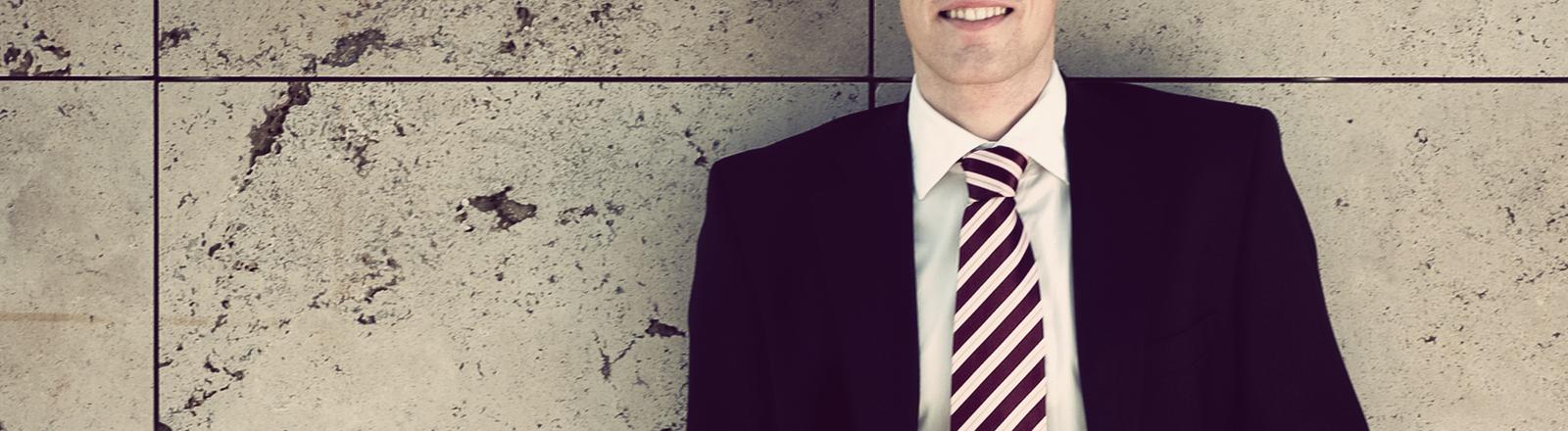 Irgendein Typ im schicken Anzug ist an eine Wand gelehnt.
