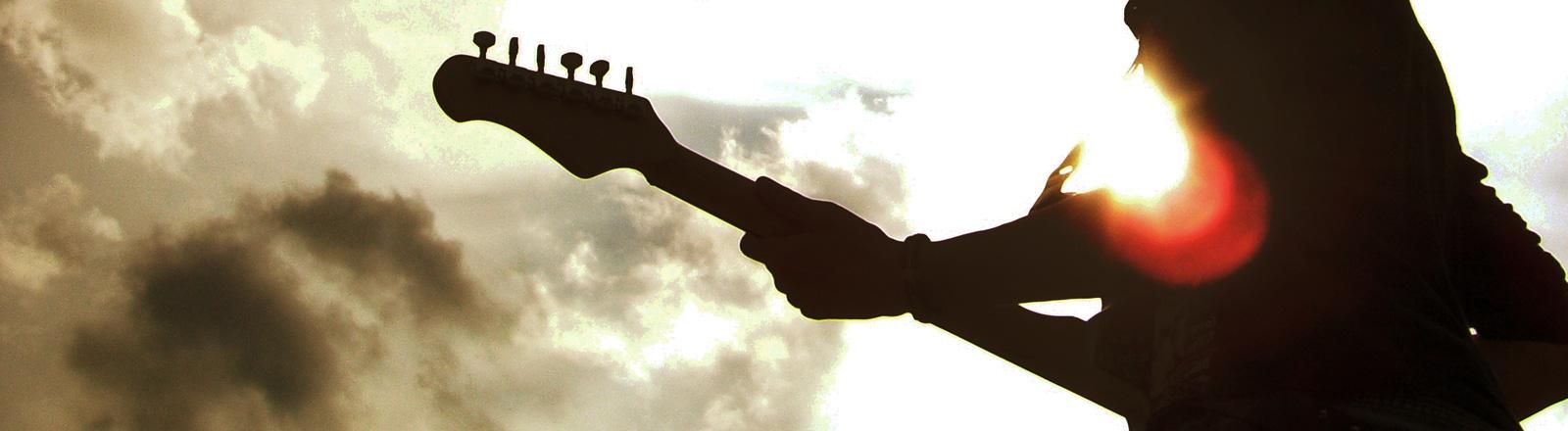 Mann mit Gitarre steht im Sonnenlicht, nur seine Silhouette ist sichtbar.