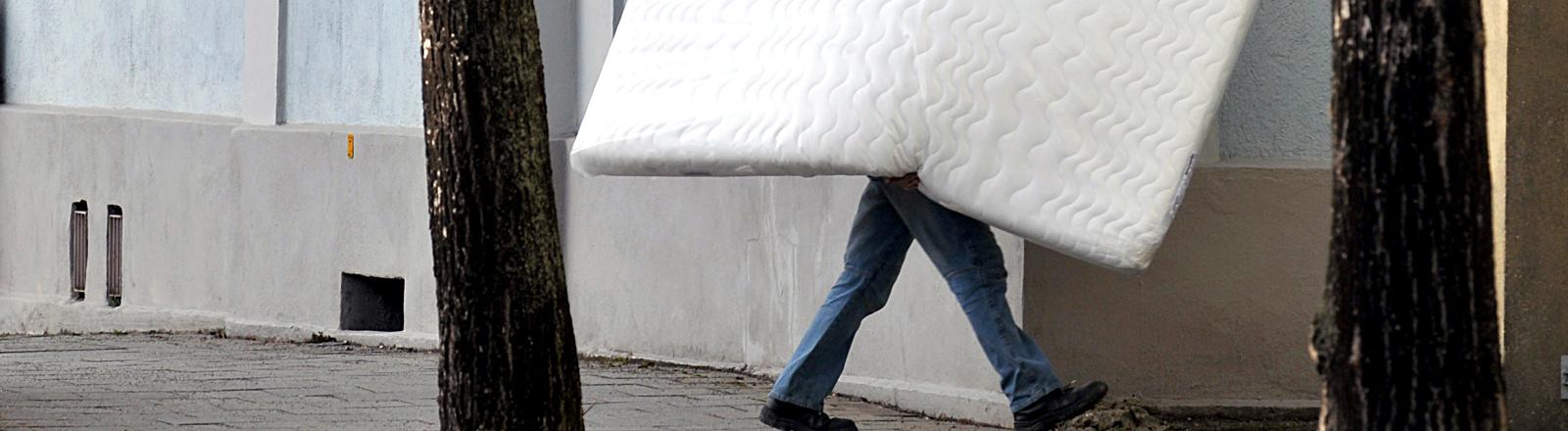 Ein Mann trägt einen Matratze auf der Straße.
