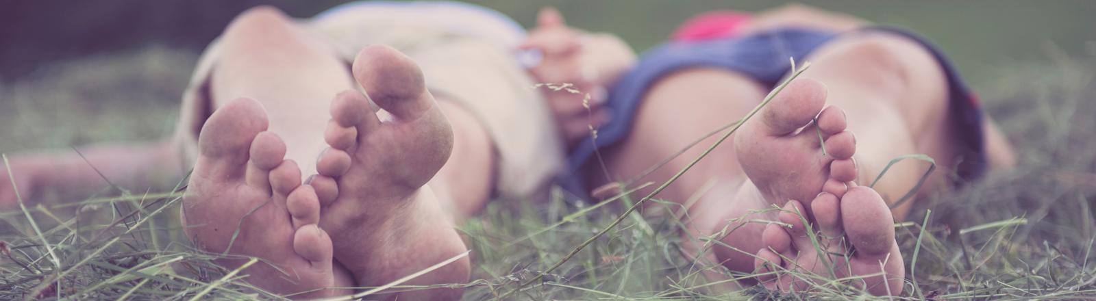 Ein Paar liegt barfuß im Gras und hält sich an den Händen.