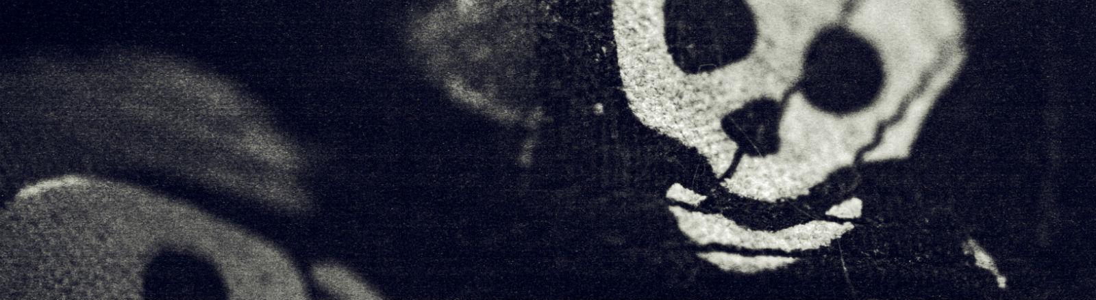 Auf ein schwarzes Tuch sind weiße Totenköpfe gedruckt.
