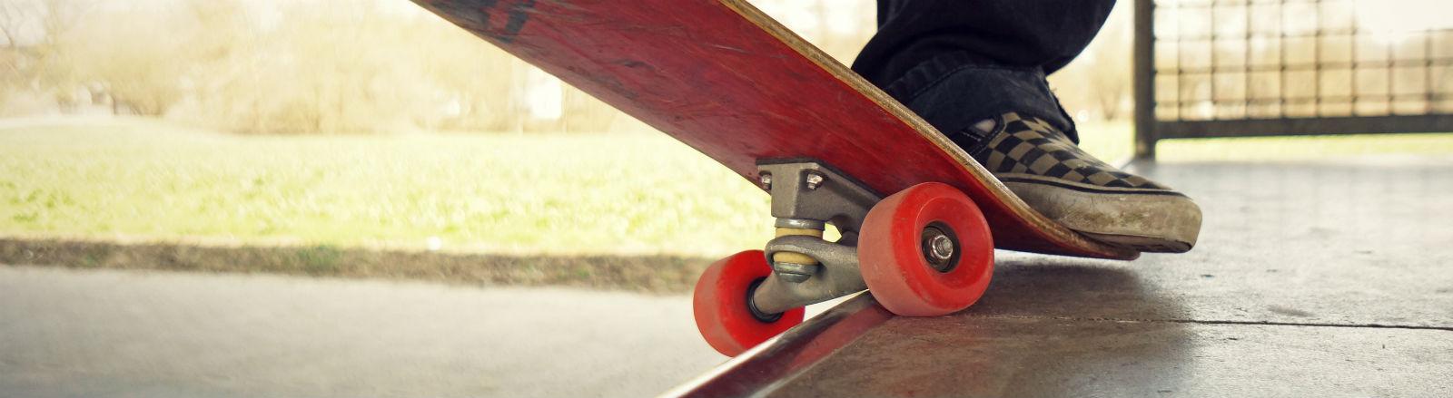 Ein Skater steht auf einem Skateboard, in Jeans und Karoschuhen,