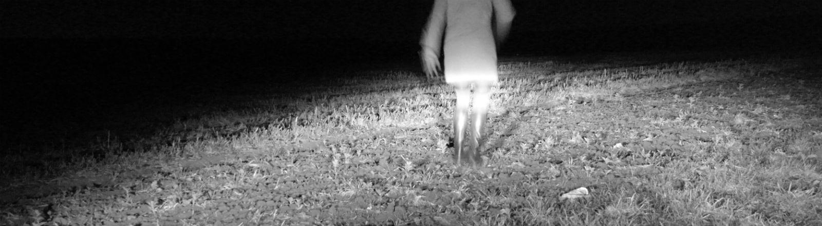 Eine Frau läuft auf einem Feld weg vom Betrachter.