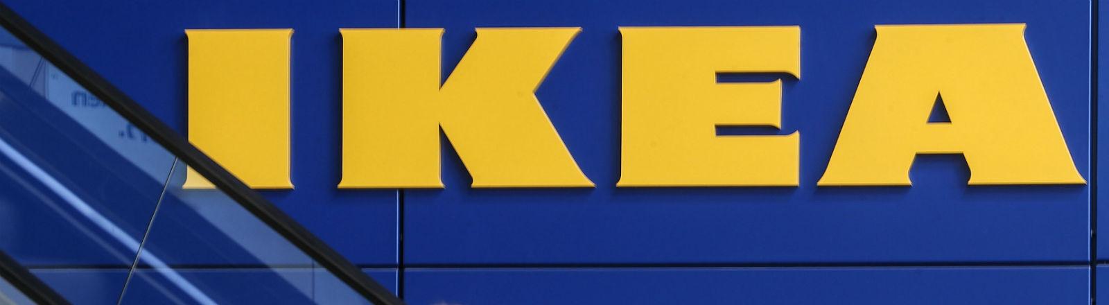 Zwei Frauen auf einer Rolltreppe blicken zum Ikea-Schriftzug hoch. Bild: dpa