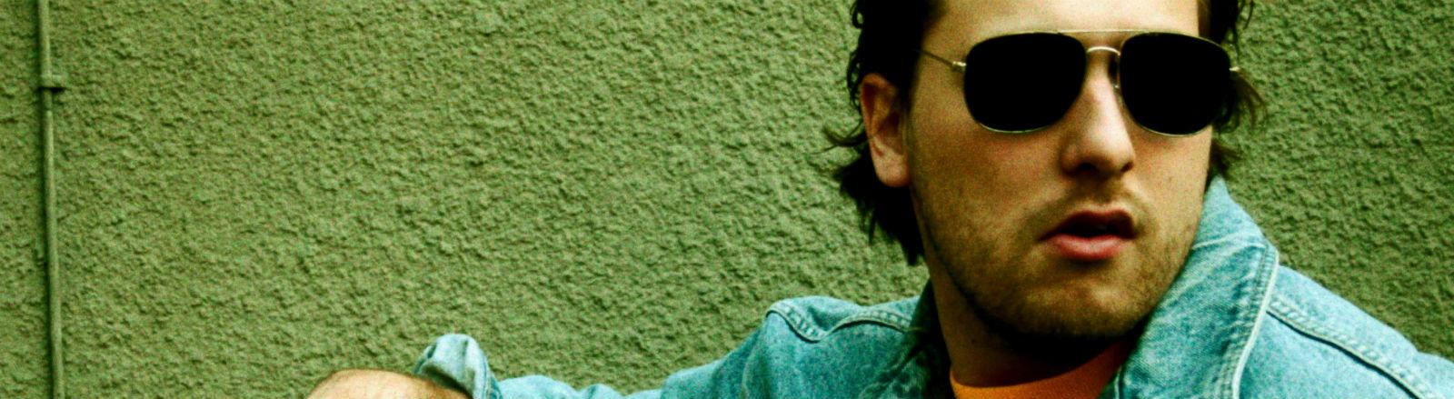 Ein Mann mit Sonnenbrille und Jeansjacke lehnt an einer Wand.