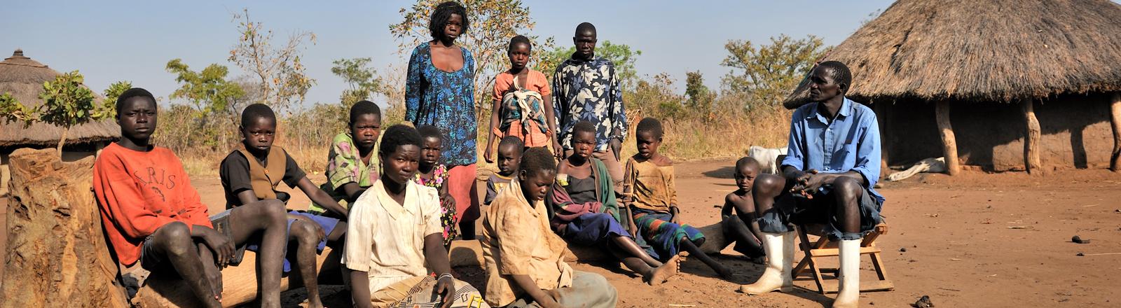 Der Bauer Ociti Augustino Languna (rechts) sitzt am 18.01.2012 mit seiner Familie vor seiner Hütte an Rande von Kitgum in Norduganda. 15 seiner 24 Kinder leiden am Kopfnicken-Syndrom. Das Syndrom ist eine neue, unbekannte Krankheit, die das erste Mal in den 80er Jahren im Sudan aufgetreten ist. Erkrankte sind mental und physisch stark eingeschränkt, wobei nur Kinder zwischen fünf und 15 Jahren betroffen sind.