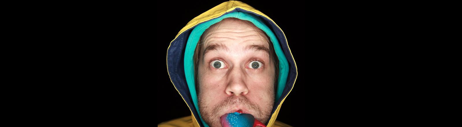 Ein Mann reißt die Augen auf und hat einen Plastikfisch im Mund stecken.