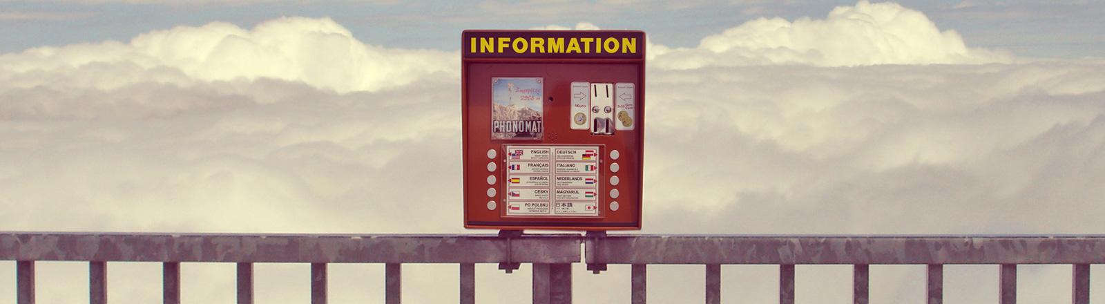 Ein roter Automat steht auf einem Geländer. Touristen können Informationen in verschiedenen Sprachen abrufen. Dahinter sind Wolken.