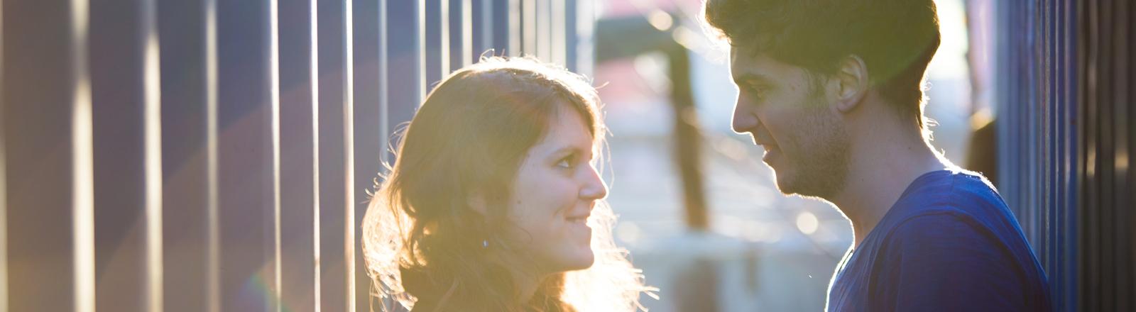 Eine Frau und ein Mann lächeln sich an.