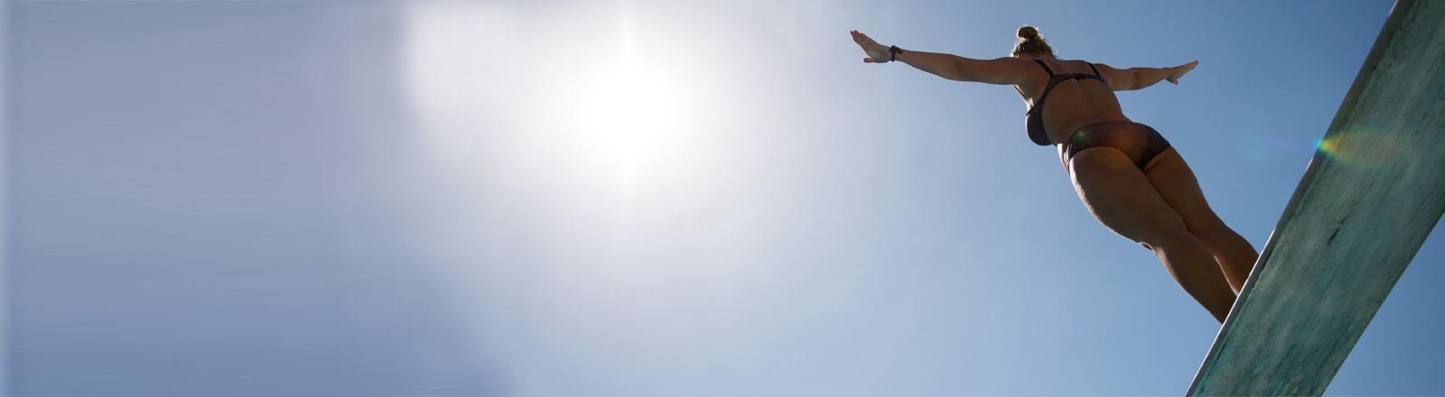 Maria (28) steht am 04.06.2015 im Schwimmbad Billstedt in Hamburg auf dem Drei-Meter-Brett und bereitet sich auf den Sprung vor.