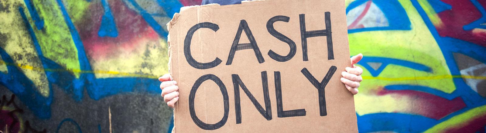 """Ein Mann der eine Stück Pappe in der Hand hält, auf dem """"Cash Only"""" steht"""
