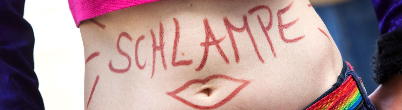 """Eine Frau, die an einem Slutwalk teilnimmt und sich das Wort """"Schlampe"""" auf den Bauch geschrieben hat."""