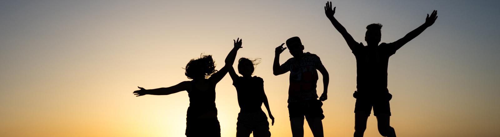 Studenten springen vor einem Sonnenuntergang in die Luft.