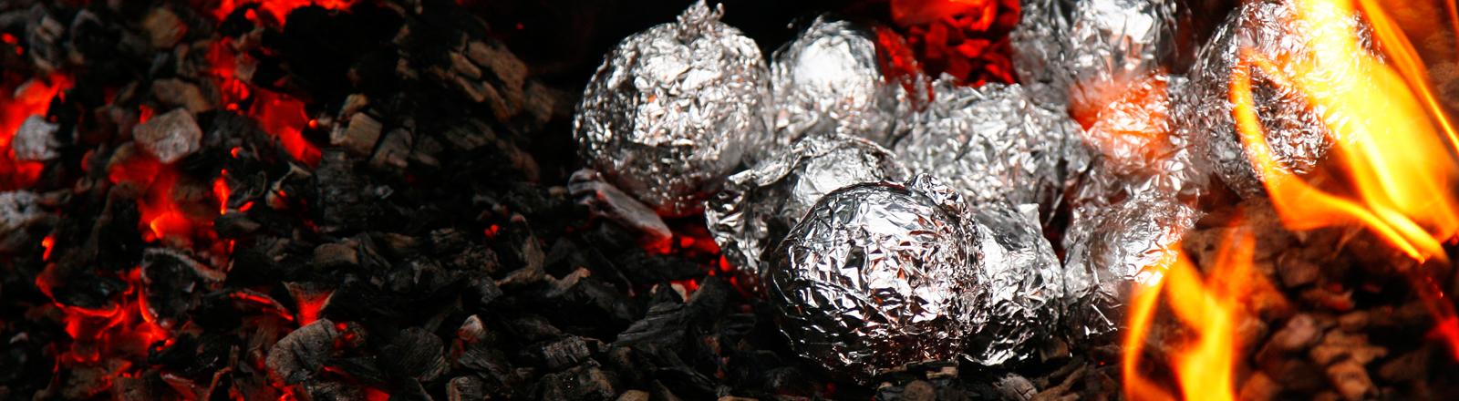 In Alufolie verpackte Kartoffeln liegen auf glühenden Kohlen.