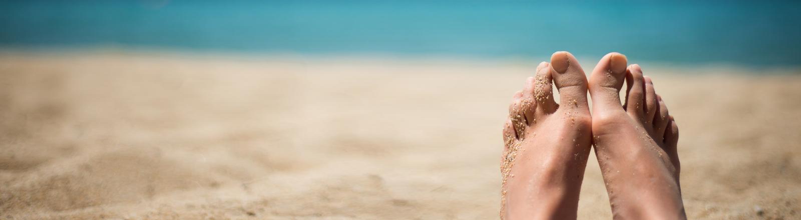 Zwei nackte Füße, ein Strand, herrliches, blaues Wasser. Sieht nach Urlaub aus.