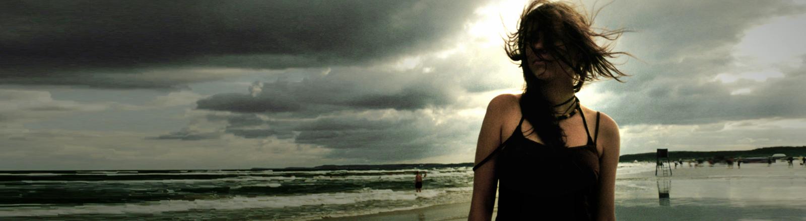 Eine Frau steht an einem stürmischen Tag am Strand.