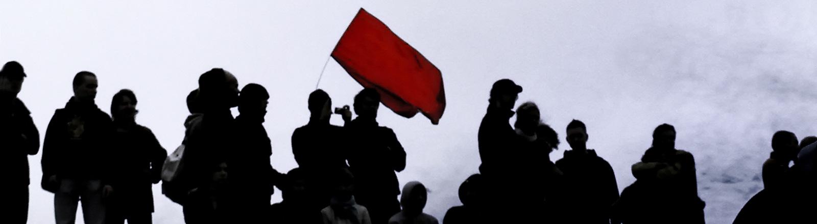 Eine Gruppe von Menschen in schwarzer Kleidung steht zusammen. Einer hält eine rote Fahne in den Himmel.