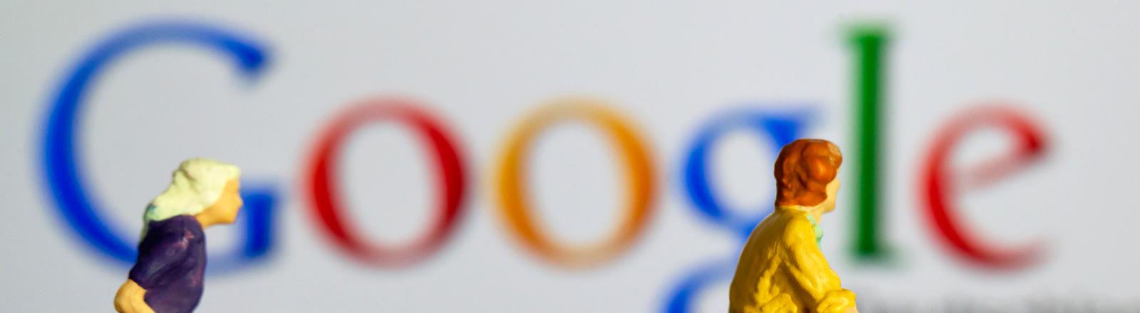 Figuren von einem Mann und einer Frau mit Einkaufswagen vor dem Google-Logo.