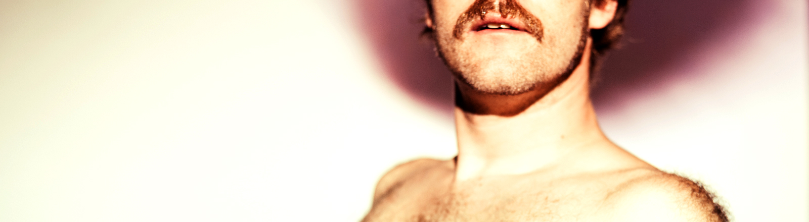 Ein behaarter Mann mit Schnauzbart trägt ein enges Oberteil. Man sieht seine Brust.